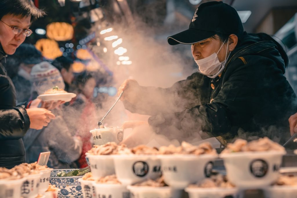 A man serves hot soup at a street trader stall; he wears a mask whilst serving, so is aware of the need for good street food hygiene.